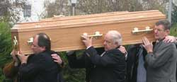 Relatives of Fr Con carrying his coffin in the cemetery
