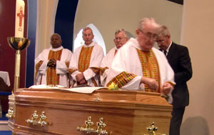 Bishop John Moore SMA blessing the coffin during the obsequies