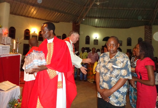 Fr Masimishila and Fr Barry receive gifts for the poor during the closing Mass